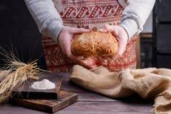 Rond artisanaal brood in de handen van een bakker Het concept gezond voedsel en traditionele bakkerij stock foto's