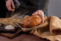 Rond artisanaal brood in de handen van een mensenclose-up Het concept gezond voedsel en traditionele bakkerij royalty-vrije stock foto