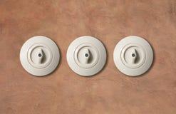 Rond blanc de vintage de trois commutateurs avec le bouton sur le contexte brun clair de mur de stuc plan rapproché, détails Photographie stock