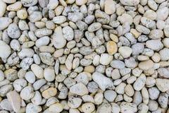 Rond gemaakte stenen wit en grijs op strand als achtergrond Stock Foto