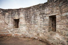 Rond geruïneerd binnenland met lege vensters van oud steenfort Stock Fotografie