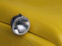 Rond hoofdlicht op gele auto stock foto