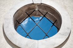 Rond middeleeuws venster met mening van de bars de blauwe hemel - Abstracte Conceptenachtergrond - binnen in openlucht Concept -  stock fotografie