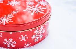 Rond, rood koekje en gebakken die het tincontainer van het goederenaluminium met het witte patroon van de sneeuwvlokdruk wordt ve Stock Fotografie
