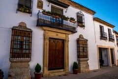 RONDA ANDALUSIA/SPANIEN - OKTOBER 08 2017: VITA HUSET MED METALLBALKONGEN OCH TRÄDÖRREN Royaltyfri Bild