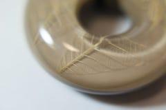 Ronda marrón gris de piedra el étnico con la hoja dentro Imagen de archivo libre de regalías
