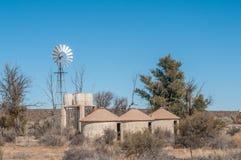 Rondavels bredvid en windpump och vattenlagringsbehållare Royaltyfri Fotografi