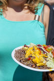Rondborstig meisje die smakelijke paella tonen Stock Fotografie