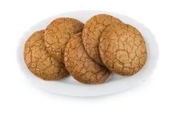 Ronde bruine die koekjes in plaat op wit wordt geïsoleerd Stock Foto's