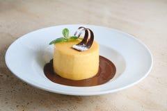 Ronde cake met gematigde chocolade op witte plaat Stock Foto