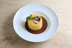 Ronde cake met gematigde chocolade op witte plaat Stock Foto's