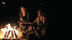 Ronde camerabeweging: multiraciale groep jongeren die door het vuur laat bij nacht en het zingen liederen, het spelen zitten stock footage