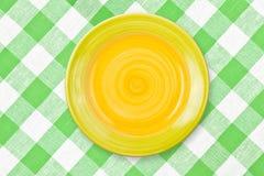 Ronde gele plaat op groen gecontroleerd tafelkleed Royalty-vrije Stock Foto