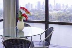 Ronde glaslijst met zwarte stoel met witte vaas, rode bloem o Royalty-vrije Stock Foto's