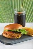 Ronde hamburger met kippenkotelet en Frieten en een glas royalty-vrije stock afbeelding