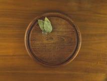 Ronde houten scherpe raad met notemuskaat en baaibladeren stock foto's