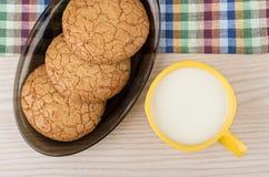 Ronde koekjes in zwarte schotel en kop van melk op lijst Royalty-vrije Stock Afbeeldingen