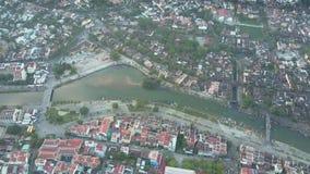 Ronde luchtmotie kalme rivier tussen stadsdelen met bomen stock video