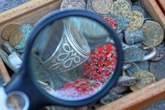 Ronde meer magnifier over een stapel van oude juwelen in een doos stock foto
