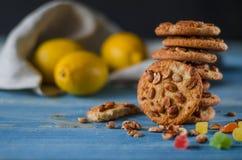 Ronde oranje koekjes met kleurrijke gekonfijte vruchten en een plak van sappige sinaasappel die op een houten lijst liggen stock afbeelding