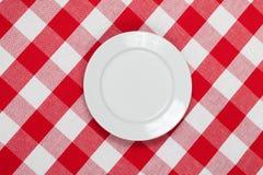 Ronde plaat op rood gecontroleerd tafelkleed Stock Foto's