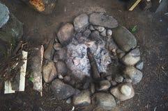 Ronde steen bosopen haard met steenkool en houten as Bostribunekamp van jagers en toeristen stock afbeeldingen