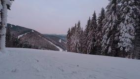 Ronde timelapse Skiërs en snowboarders die onderaan de helling bij een skitoevlucht gaan stock videobeelden
