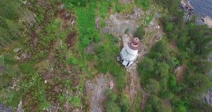 Ronde vlucht over vuurtoren op rotsachtige kaap aan reusachtig meer stock video
