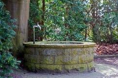 Ronde waterput met tapkraan in een begraafplaats met oude bomen Stock Afbeelding