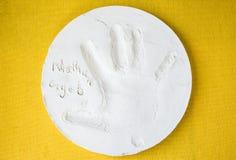 Ronde witte kleischotel met een kleine child& x27; s handprint Stock Foto