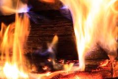 Rondin brûlant avec les flammes oranges et bleues Photographie stock libre de droits