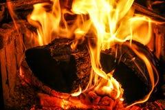 Rondins brûlant chauds dans l'endroit du feu Photographie stock