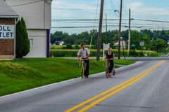 Ronks, Amish country, PA 27 Julay 2017 a man and a woman riding on amish style` scooters stock image