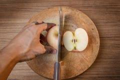 Rood appel en Mes op houten scherpe raad Stock Afbeeldingen
