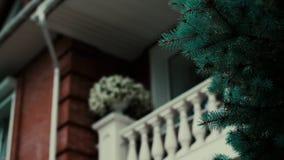 Rood baksteenbuitenhuis met uitstekende kolommen en blauwe sparren in de tuin stock video