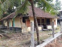 Rood betegeld huis in een dorp stock fotografie
