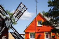 Rood blokhuis en bruine decoratieve molenwind Stock Afbeelding