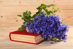 Rood boek en boeket van korenbloemen op houten achtergrond Royalty-vrije Stock Foto