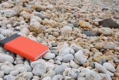 Rood boek op kiezelsteen Stock Foto's