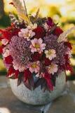 Rood de herfstboeket van rozen, chrysanten en veren in een vaas van pompoen Stock Afbeelding