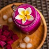 Rood die Draakvruchtensap in een glas, met Plumeria-bloem, het fruit van de besnoeiingsdraak en ijsblokjes wordt verfraaid Royalty-vrije Stock Foto's