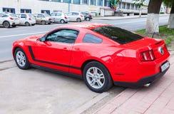 Rood die Ford Mustang omhoog bij de stadsstraat wordt geparkeerd in de zomerdag Stock Foto's