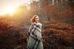 Rood die haarmeisje bij zonsopgang in een rode deken wordt verpakt stock fotografie