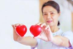 Rood die hart door vrouwelijke verpleegsters` s hand te glimlachen wordt gehouden, die gevend inspanningshoogte - de mening van d royalty-vrije stock fotografie