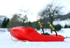 Rood die loodje van robuust plastiek op sneeuw wordt gemaakt royalty-vrije stock afbeeldingen