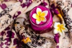 Rood Draakvruchtensap in een glas, dat met Plumeria-bloem over bloemrijke stof wordt verfraaid Hoogste mening Stock Foto
