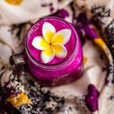 Rood Draakvruchtensap in een glas, dat met Plumeria-bloem over bloemrijke stof wordt verfraaid Hoogste mening Vierkant beeld Stock Fotografie