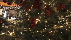 Rood eekhoornspeelgoed en witte lichte slinger op Kerstmisboom in openlucht stock footage