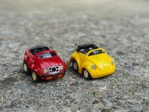 Rood en geel stuk speelgoed parkeerterrein op ruwe cementweg Royalty-vrije Stock Fotografie