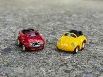 Rood en geel stuk speelgoed parkeerterrein op ruwe cementweg Royalty-vrije Stock Foto